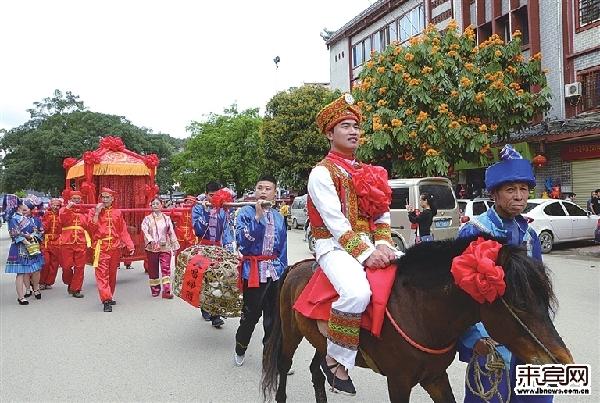 """迎亲队伍敲锣吹唢呐,穿行古城。 """"新郎""""骑着披红挂彩的高头大马,领着抬花轿的队伍从莫土司衙署出发迎娶""""新娘"""",浩浩荡荡的迎亲队伍敲着锣鼓、吹奏唢呐穿行古城,好不热闹……这是4月8日在忻城县土司古城举行的一场传统壮族婚礼展演活动,原汁原味的壮族婚俗为""""三月三""""增添不少喜气。"""
